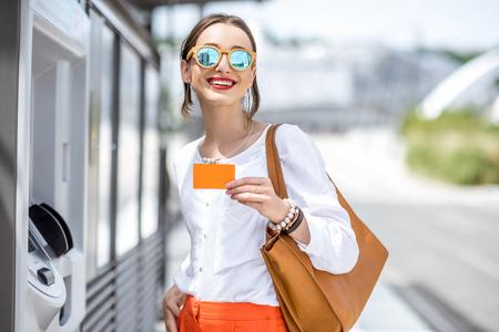 Foto de Woman buying a ticket or using ATM outdoors - Imagen libre de derechos