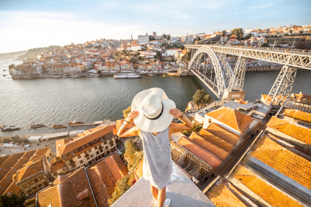 Foto de Young woman tourist enjoying beautiful landscape view on the old town with river and famous iron bridge during the sunset in Porto city, Portugal - Imagen libre de derechos