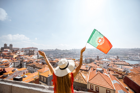 Foto de Young woman tourist in red dress standing back with portuguese flag on the old town background traveling in Porto city, Portugal - Imagen libre de derechos