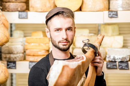 Portrait of a young contador with prosciutto leg standing in front of the store showcase full of cheeses