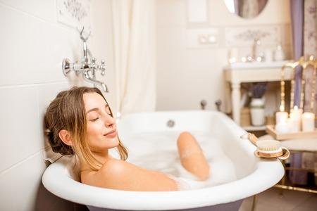 Foto de Young woman relaxing in the beautiful vintage bath full of foam in the retro bathroom decorated with candles - Imagen libre de derechos