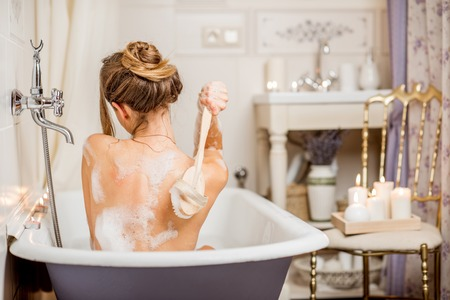 Photo pour Young woman washing with brush in the beautiful vintage bath full of foam in the bathroom decorated with candles - image libre de droit