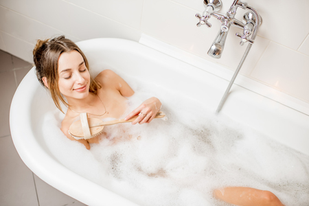 Photo pour Top view on the young woman lying with brush in the bath full of foam - image libre de droit