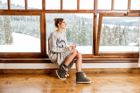 Foto de Young woman in sweater sitting near the big window at the cozy wooden mountain house with beautiful landscape view during the winter time - Imagen libre de derechos