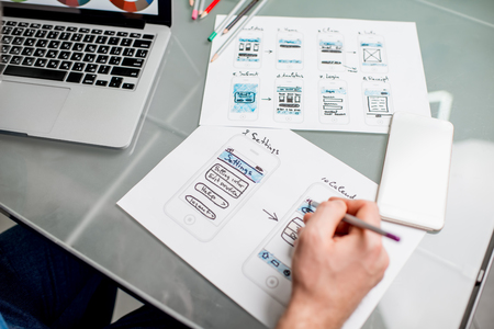 Foto de UX designer working on the mobile application experience sketching drawings at the office. Image focused no the drawsings cropped with no face - Imagen libre de derechos