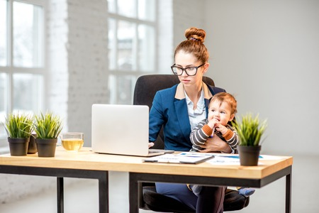 Foto de Young multitasking businessmam dressed in the suit working with laptop and documents sitting with her baby son at the office - Imagen libre de derechos