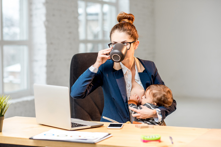Photo pour Young multitasking businessmam feeding her baby son with breast while having a break drinking coffee at the office - image libre de droit