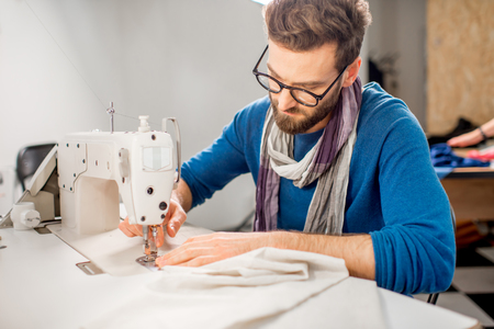 Photo for Handsome tailor sewing fabric with a sewing machine at the studio - Royalty Free Image