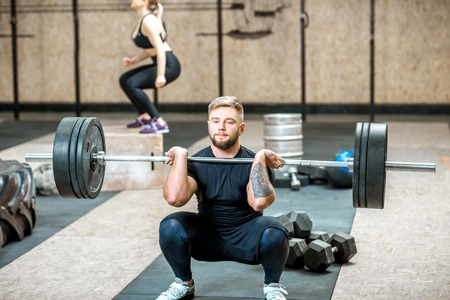 Foto de Handsome athletic man in black sports wear lifting up a heavy burbell with woman training on the background in the crossfit gym - Imagen libre de derechos