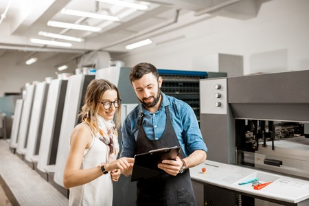 Photo pour Young woman designer and print operator working together at the print manufacturing with offset machine on the background - image libre de droit