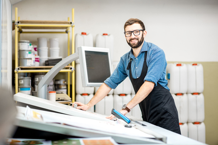 Photo pour Portrait of a male worker standing near the operating desk of the printing manufacturing - image libre de droit