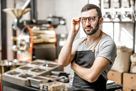 Portrait of a handome bearded barista in uniform standing in the coffee shop with coffee roaster machine on the bckground