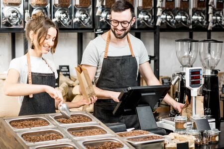 Two sellers in uniform filling bags with coffee beans while working in the coffee store