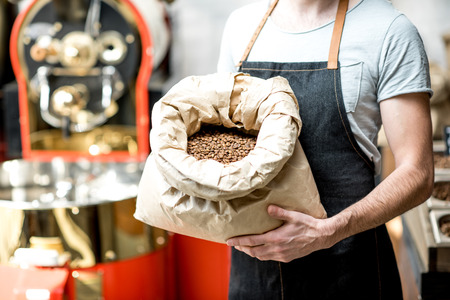 Barista holding bag full with roasted coffee beans at the coffee store