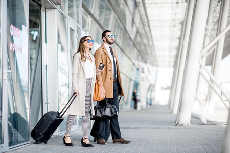 Foto de Business couple in coats walking out the airport with luggage during the business trip - Imagen libre de derechos