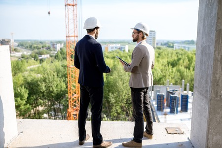 Photo pour Two engineers or architects supervising the process of residential building construction standing on the structure outdoors - image libre de droit