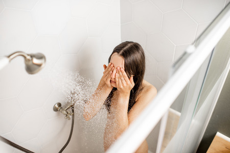 Photo for Young and beautiful woman washing her face, taking a shower in the white cabin. View from above - Royalty Free Image