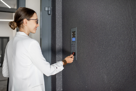 Foto de Young business woman in white suit touching the intercom with keychain opening the door of residential modern building - Imagen libre de derechos