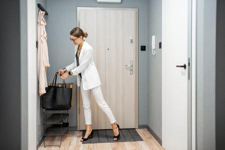 Foto de Young business woman at the hall of the apartment returning after the job - Imagen libre de derechos