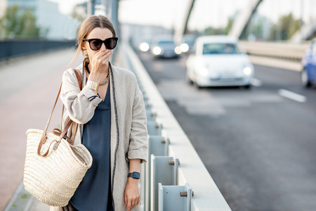 Photo pour Woman closing her nose feeling bad because of the air pollution on the bridge with traffic in the city - image libre de droit