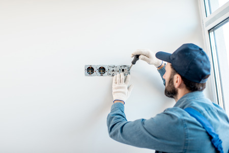 Photo for Electrician in uniform mounting electric sockets on the white wall indoors - Royalty Free Image