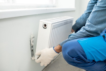 Photo for Workman mounting water heating radiator on the white wall indoors, close-up view - Royalty Free Image