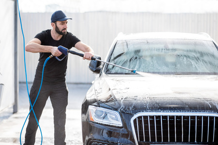 Photo pour Professional washer in black uniform washing luxury car with water gun on an open air car wash - image libre de droit