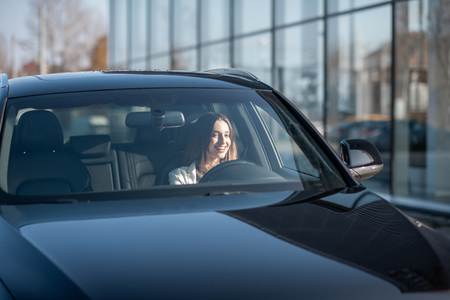 Photo pour Young businesswoman driving a luxury car, view from the outside through the windshield - image libre de droit