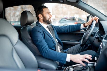 Foto de Handsome bearded businessman dressed in the suit driving a car in the city - Imagen libre de derechos