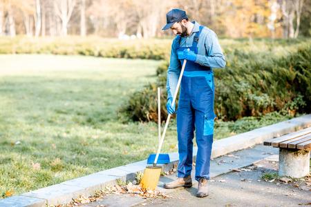 Foto de Professional sweeper in uniform sweeping leaves with broom and scoop on the street - Imagen libre de derechos