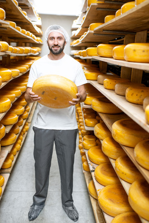Portrait of a handsome worker standing with cheese at the storage full of cheese wheels during the aging process