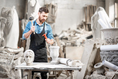 Photo pour Portrait of a handsome sculptor in blue t-shirt and apron working with stone sculptures on the table at the old atmospheric studio - image libre de droit