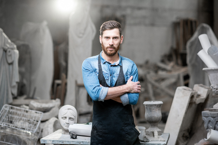 Photo pour Portrait of a handsomme sculptor in blue t-shirt and apron standing in the studio with old sculptures on the background - image libre de droit