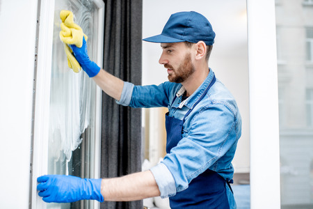 Photo for Man as a professional cleaner in blue uniform washing window with cotton wiper indoors - Royalty Free Image