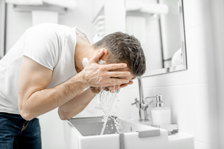 Photo pour Man washing his face with fresh water and foam in the sink at the white bathroom - image libre de droit