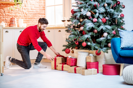Photo pour Man putting gifts under the Christmas tree preparing for a New Year holidays at home - image libre de droit