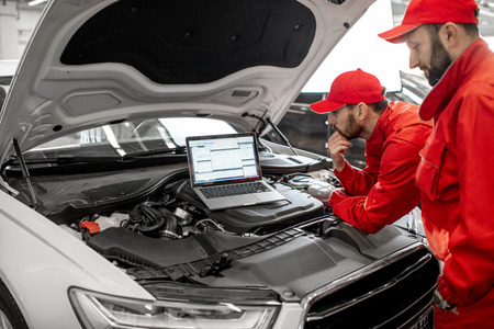 Photo pour Two auto mechanics in red uniform doing engine diagnostics with computer in the car service - image libre de droit