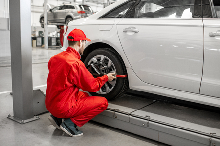 Photo pour Handsome auto mechanic in red uniform fixing disk for wheel alignment at the car service - image libre de droit