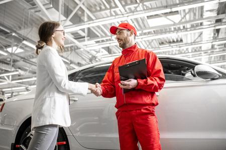 Photo pour Young woman client shaking hands with auto mechanic in red uniform having a deal at the car service - image libre de droit