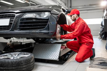 Photo pour Auto mechanic in red uniform servicing sports car checking front brakes in the car service - image libre de droit