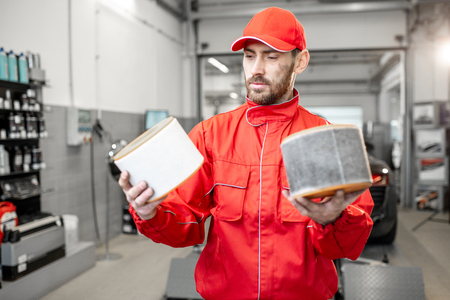 Photo pour Auto mechanic in red uniform holding new and used air filter standing at the car service - image libre de droit
