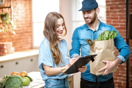 Photo pour Courier service worker delivering fresh food to a happy woman client signing some documents on the kitchen at home - image libre de droit