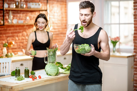 Foto de Young sports couple having snack with healthy salad and green smoothie on the kitchen at home - Imagen libre de derechos