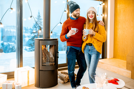 Photo pour Young couple dressed in bright sweaters and hats standing together with hot drinks near the fireplace in the modern house durnig winter time - image libre de droit
