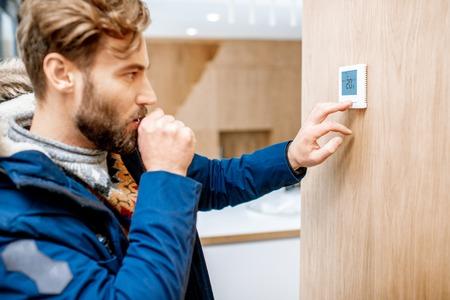 Foto de Man in winter clothes feeling cold adjusting room temperature with electronic thermostat at home - Imagen libre de derechos