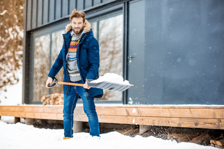 Foto de Handsome man in winter clothes cleaning snow with a shovel near the modern house in the mountains - Imagen libre de derechos