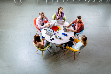 Photo pour Team of a young coworkers dressed casually working together with laptops sitting at the round table in the office, view from above - image libre de droit