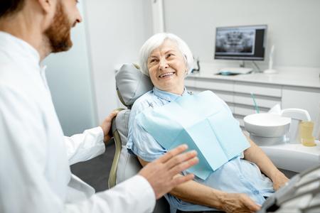 Foto für Beautiful elder woman with healthy smile sitting during the consultation with dentist at the dental office - Lizenzfreies Bild