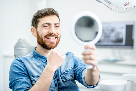 Photo pour Portrait of a handsome bearded man with healthy smile in the dental office - image libre de droit