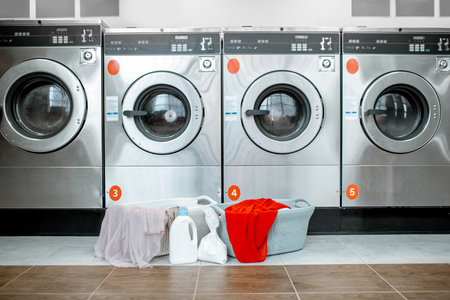 Photo pour Professional washing machines with baskets full of clothes at the self-service laundry - image libre de droit